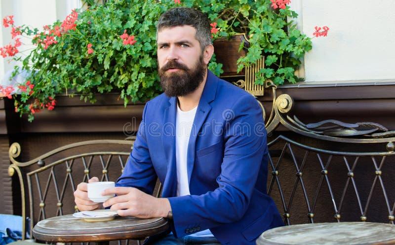 穿戴女孩褂子早晨白色的咖啡杯 有胡子的成熟人放松在咖啡馆 准备在浪漫日期 残酷有胡子的行家饮料咖啡 库存照片