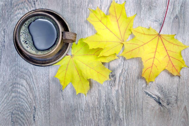 穿戴女孩褂子早晨白色的咖啡杯 槭树和一杯咖啡黄色秋叶  复制空间 顶视图 免版税图库摄影