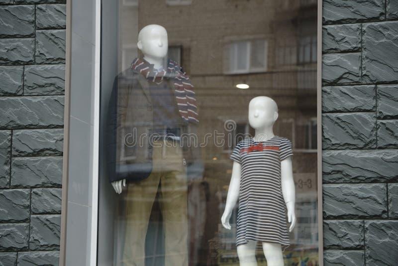 穿戴时装模特,商城,通过新的衣裳在购物期间,五颜六色的妇女` s在一家零售店的木挂衣架穿戴 免版税库存图片