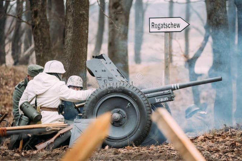 穿戴的再enactors, WWII的德国士兵装载大炮壳 免版税库存图片