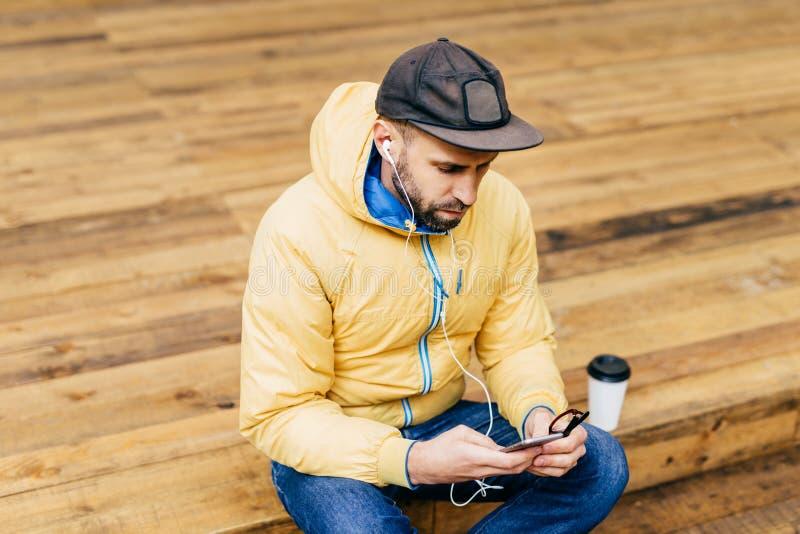 穿救生服、时髦的黑盖帽和牛仔裤的行家年轻有胡子的人坐在举行智能手机听的木地板 库存照片