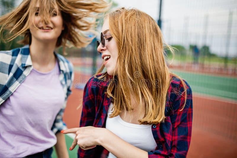 穿方格的衬衣的两个相当微笑的白肤金发的女孩在sportsfield站立并且获得乐趣 体育和凉快 库存图片