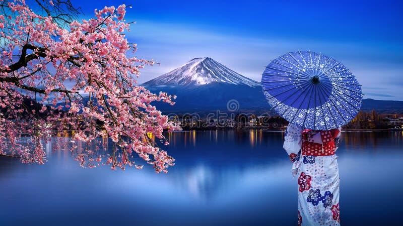 穿日本传统和服的亚裔妇女在富士山和樱花,Kawaguchiko湖在日本 免版税库存图片