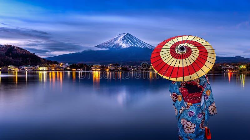穿日本传统和服的亚裔妇女在富士山,Kawaguchiko湖在日本 免版税库存照片