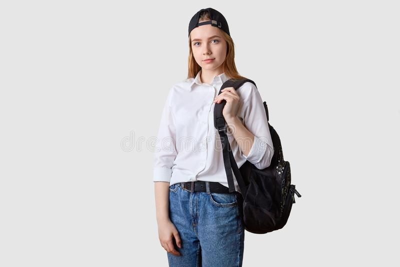 穿时兴的牛仔裤nad白色衬衫的美丽的学生女孩的图象,走到从家的学院,运载的背包, 库存照片