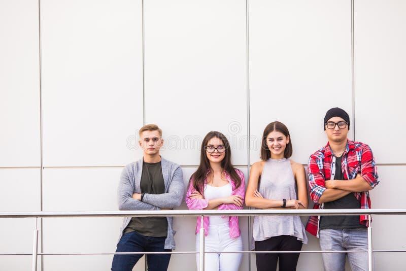 穿时髦的便衣的小组四年轻微笑的人看站立在轻的办公室或大学的照相机 免版税图库摄影