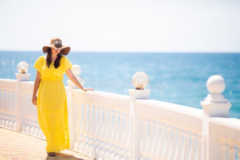 穿时髦的太阳镜、草帽和黄色礼服的愉快的年轻女人生活方式画象  免版税图库摄影