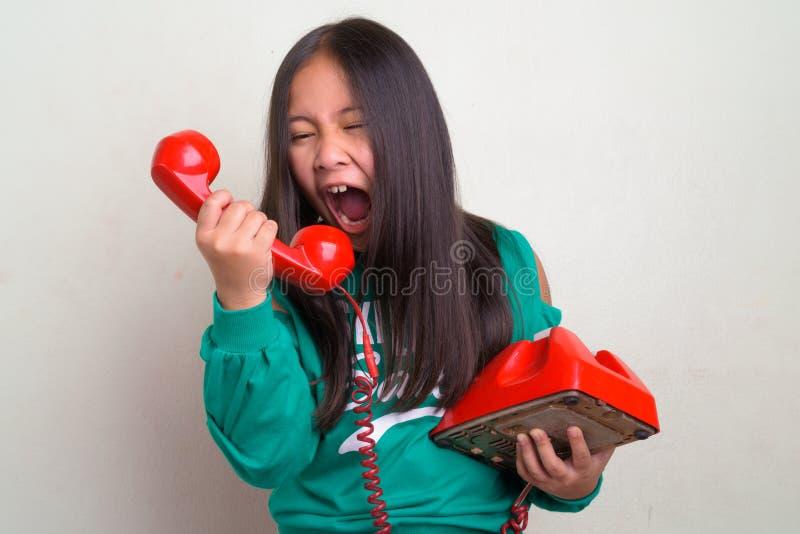 穿时髦的衣裳的年轻逗人喜爱的亚裔女孩画象  免版税库存图片