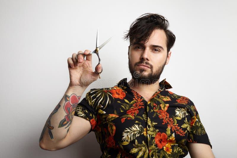 穿时髦的衬衣的画象英俊的有胡子的人掠过长头发梳 秀丽,修饰,人概念照片 免版税库存图片