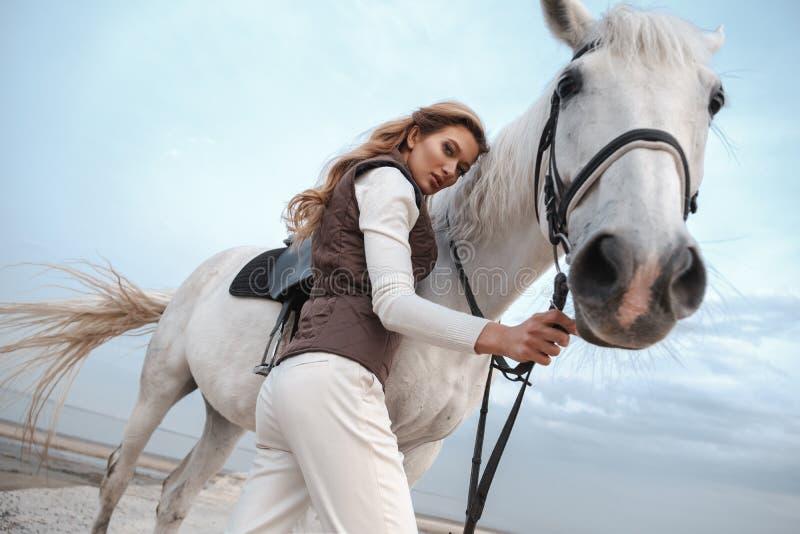 穿时髦的骑师服装的可爱和美丽的年轻女人拿着马勒并且摆在与白马 免版税库存照片