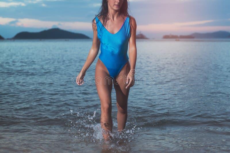 穿时髦蓝色泳装的亭亭玉立的少妇的播种的图象走在海在日落 库存照片