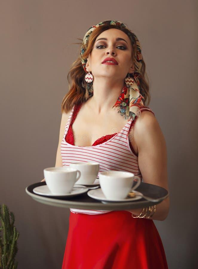 穿明亮的衣裳的美丽的年轻女人拿着盘子用咖啡 免版税图库摄影