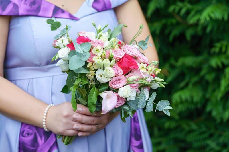 穿显示可爱宝宝爆沸和拿着婚姻的花束的一件淡紫色夏天礼服的白种人女性客人或女傧相 图库摄影