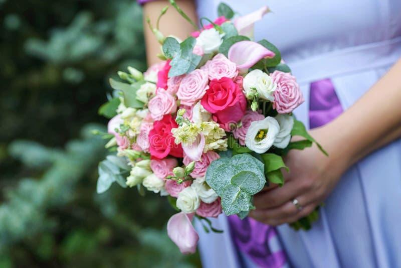 穿显示可爱宝宝爆沸和拿着婚姻的花束的一件淡紫色夏天礼服的白种人女性客人或女傧相 库存图片