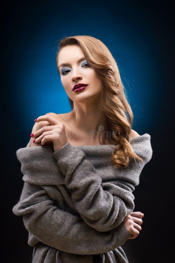 穿有一根典雅的头发的美丽的白肤金发的女孩一件灰色毛线衣 免版税库存图片