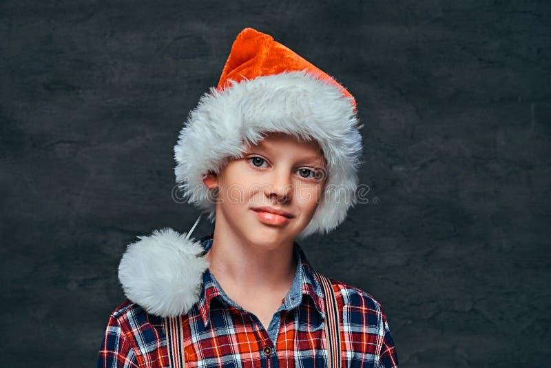 穿有悬挂装置的圣诞老人的帽子的一个英俊的青少年的男孩一件方格的衬衣 在黑暗的织地不很细背景 免版税库存照片
