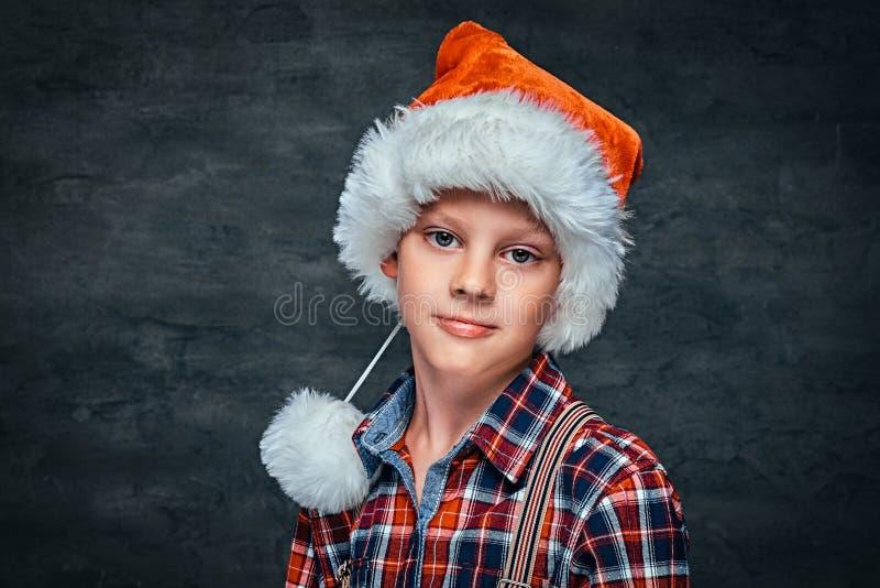 穿有悬挂装置的圣诞老人的帽子的一个英俊的青少年的男孩一件方格的衬衣 隔绝在黑暗的织地不很细背景 图库摄影