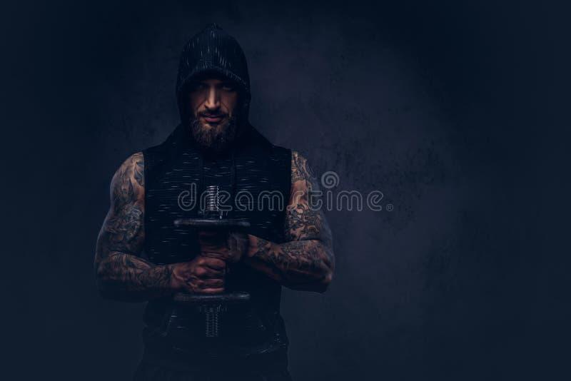 穿有敞篷的一个肌肉有胡子的tattoed男性的画象黑运动服,做与哑铃的锻炼 图库摄影