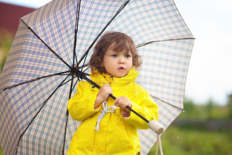 穿有方格的umrel的小孩女孩黄色防水外套 免版税库存图片