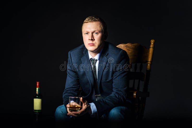 穿有杯的商人一件夹克威士忌酒坐椅子 在黑暗的演播室背景的瓶酒精 概念 库存图片