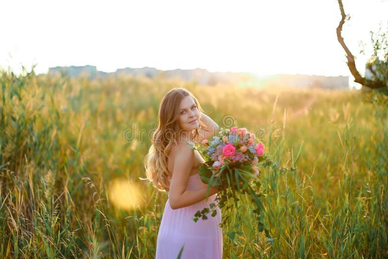 穿有站立在干草原背景中的花花束的怀孕的年轻白种人妇女桃红色礼服  库存图片