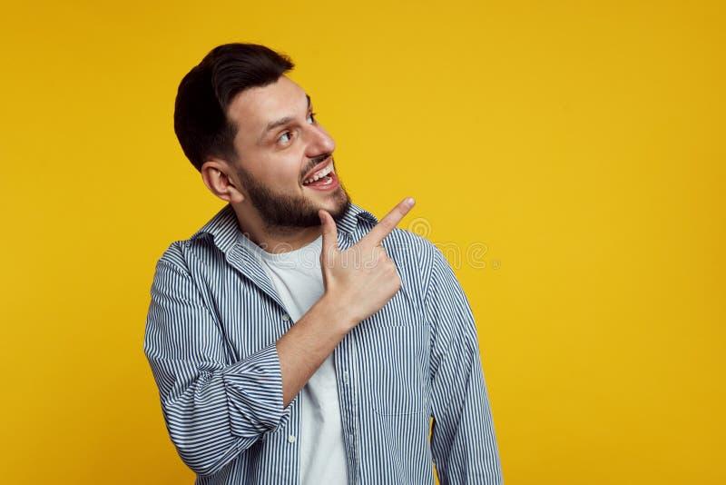 穿有线的经典衬衣和愉快地指向在橙色背景的快乐的帅哥 免版税图库摄影