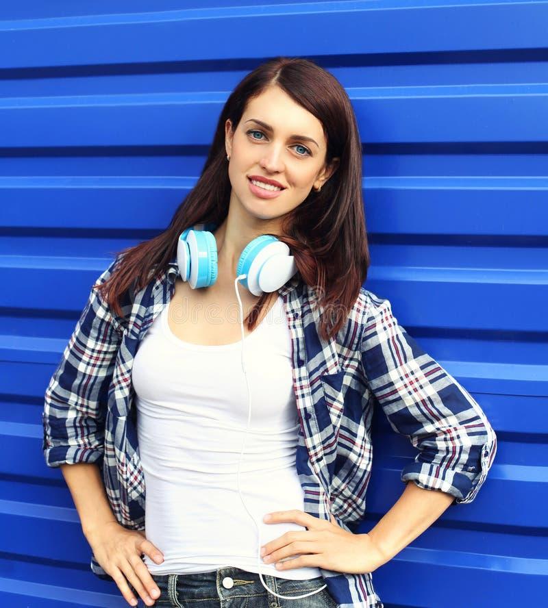 穿有耳机的俏丽的深色的妇女一件方格的衬衣在蓝色 库存图片
