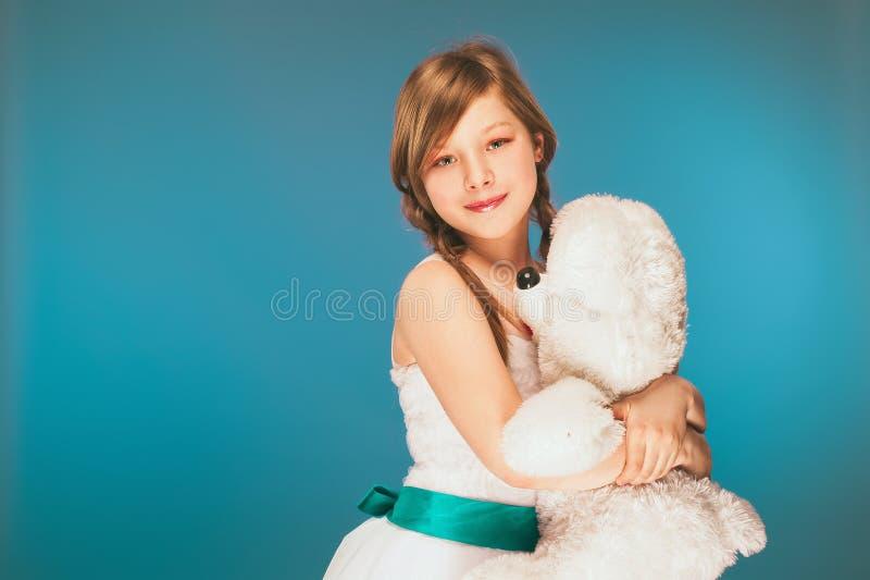 穿有逗人喜爱的微笑的女孩一件白色礼服在度假 白色玩具熊 库存图片