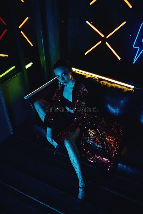 穿有闪烁的模型计算机国际庞克射击红色浴巾坐在皮革沙发反对氖 库存图片