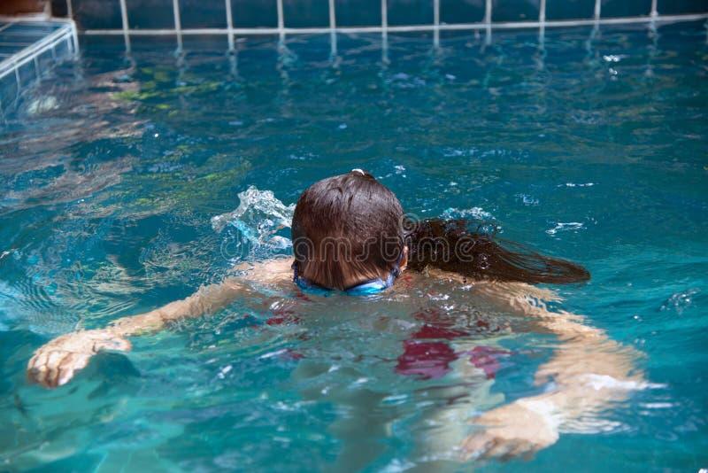 穿有防水玻璃的俏丽的亚裔妇女红色比基尼泳装游泳在游泳场 免版税图库摄影