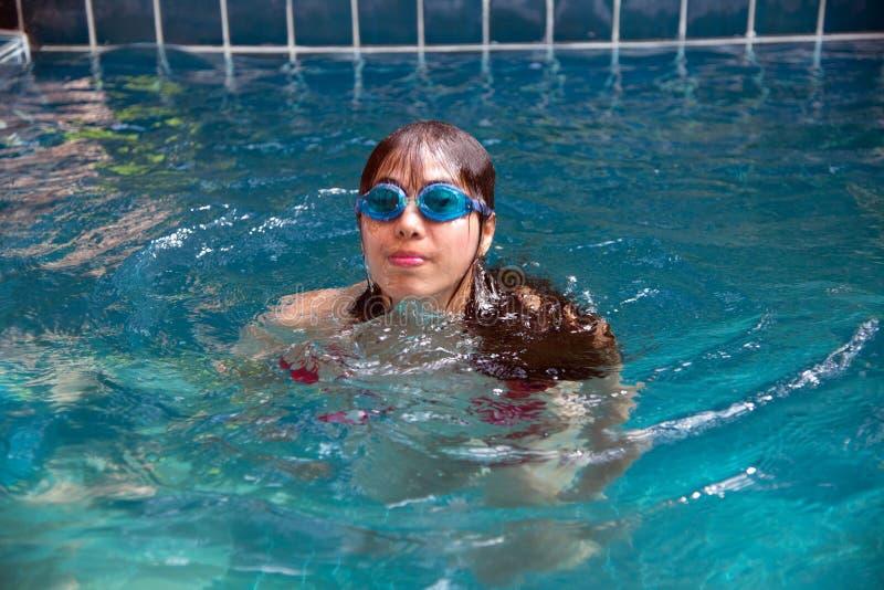 穿有防水玻璃的俏丽的亚裔妇女红色比基尼泳装游泳在游泳场 库存照片