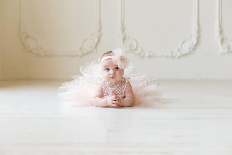 穿桃子芭蕾舞短裙的女婴 说谎在乳脂状的背景的地板上的逗人喜爱的微笑的女婴 库存图片