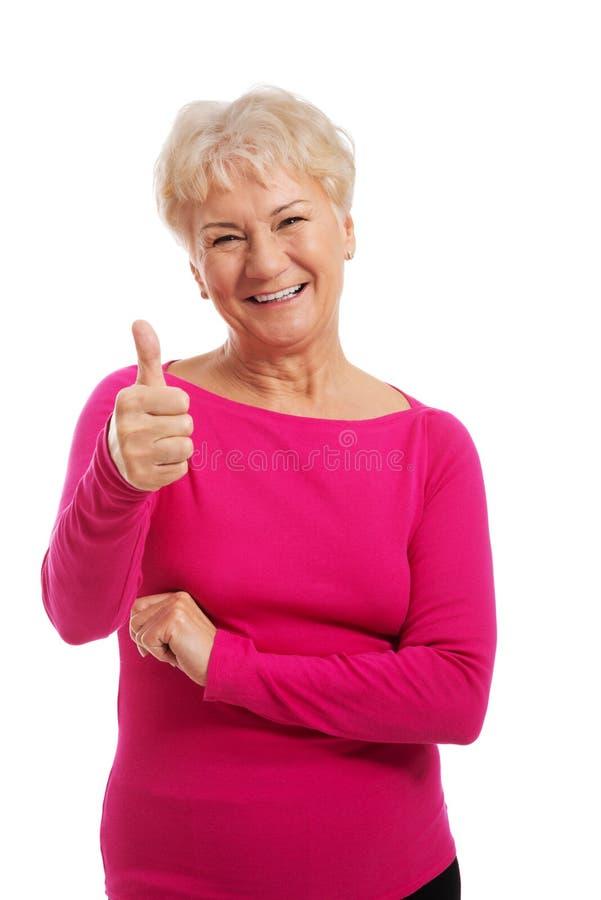 穿桃红色衬衣的一个老妇人,显示好。 库存照片