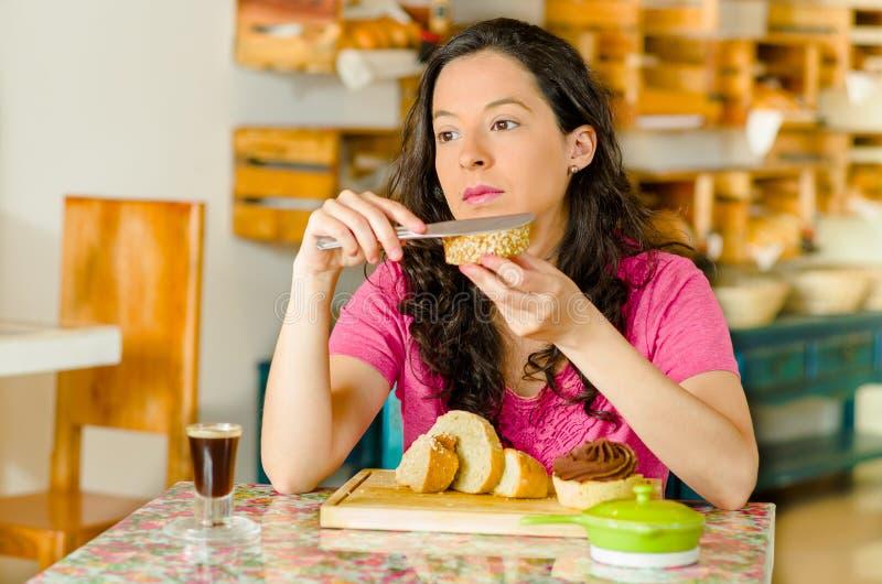 穿桃红色衬衣的俏丽的深色的妇女坐由在面包店里面的桌,应用黄油于面包片,周道 免版税图库摄影