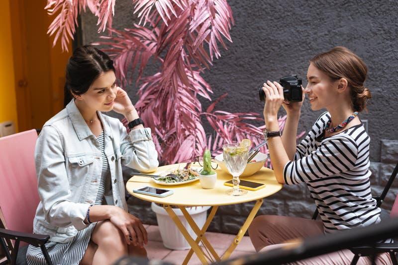 穿桃红色长裤的摄影师拍摄她的最好的朋友 免版税库存图片