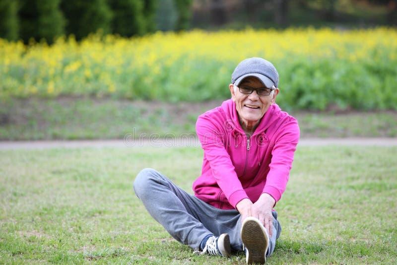 穿桃红色附头巾皮外衣的资深日本人做在草坪的一个有腿的向前弯 免版税图库摄影