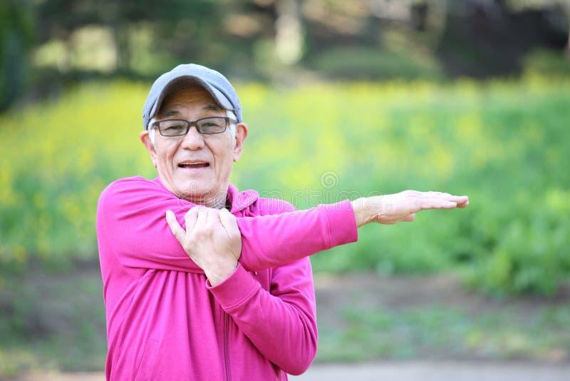穿桃红色附头巾皮外衣的资深日本人做室外胳膊的舒展 免版税库存照片