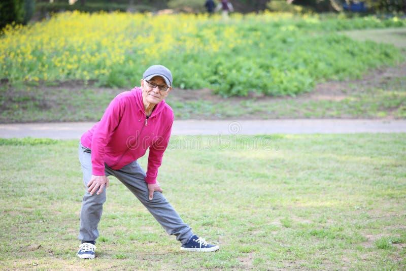穿桃红色附头巾皮外衣的资深日本人做室外腿的舒展 库存图片