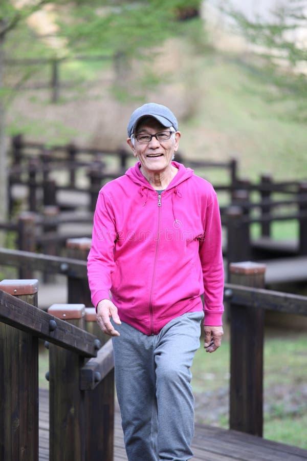 穿桃红色附头巾皮外衣的资深日本人走在木甲板在自然公园 免版税库存照片