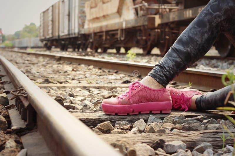 穿桃红色鞋子的妇女在火车站 免版税库存图片