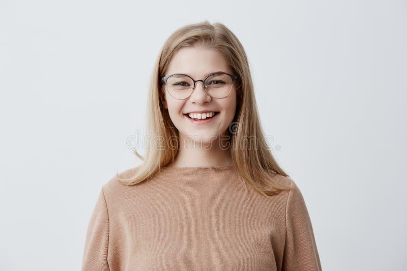 穿棕色特大毛线衣的白肤金发的嬉戏的年轻欧洲女性嘲笑有趣玩笑,展示完善的白色 库存照片
