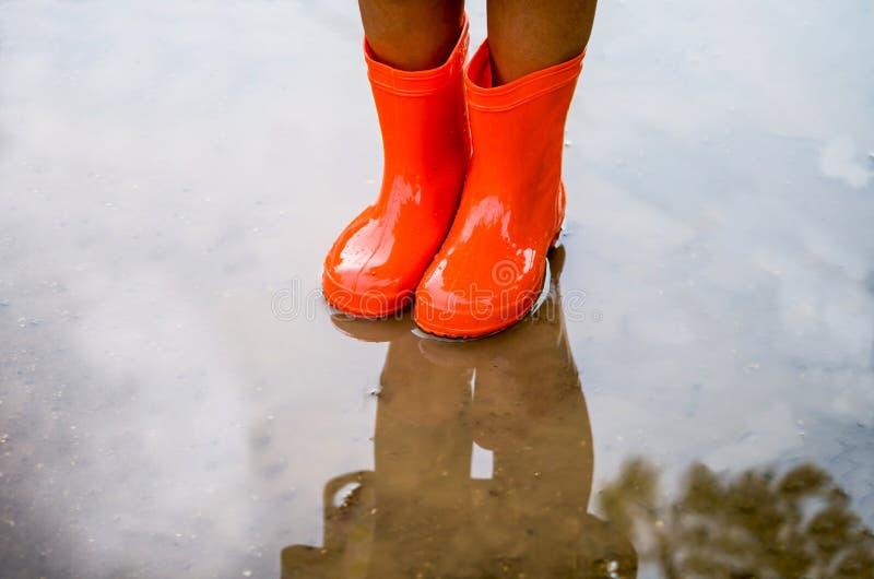 穿橙色雨靴的孩子 图库摄影
