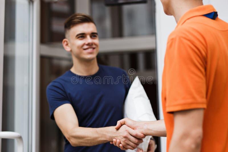 穿橙色T恤杉的人交付一个小包到一个满意的客户 友好的工作者,优质交付 免版税图库摄影