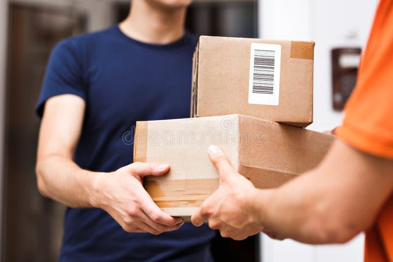穿橙色T恤杉的人交付小包到一个满意的客户 友好的工作者,优质交付 免版税图库摄影