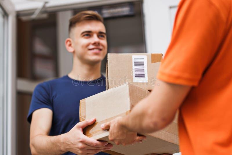穿橙色T恤杉的人交付小包到一个满意的客户 友好的工作者,优质交付 免版税库存照片