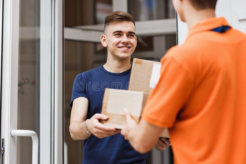 穿橙色T恤杉的人交付小包到一个满意的客户 友好的工作者,优质交付 图库摄影