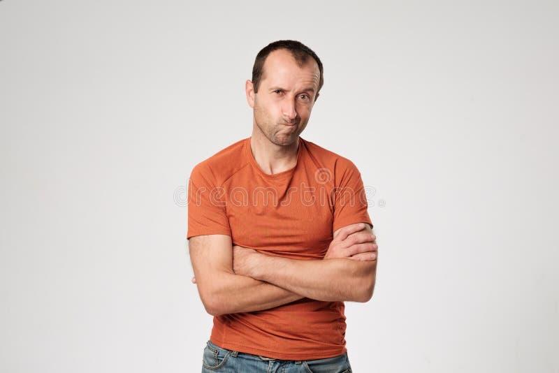 穿橙色T恤杉的恼怒的人被隔绝的画象握胳膊横渡,有怀疑和不满意的神色 免版税库存图片