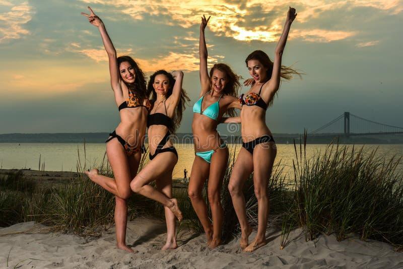 穿比基尼泳装的小组四个模型摆在日落海滩 库存图片