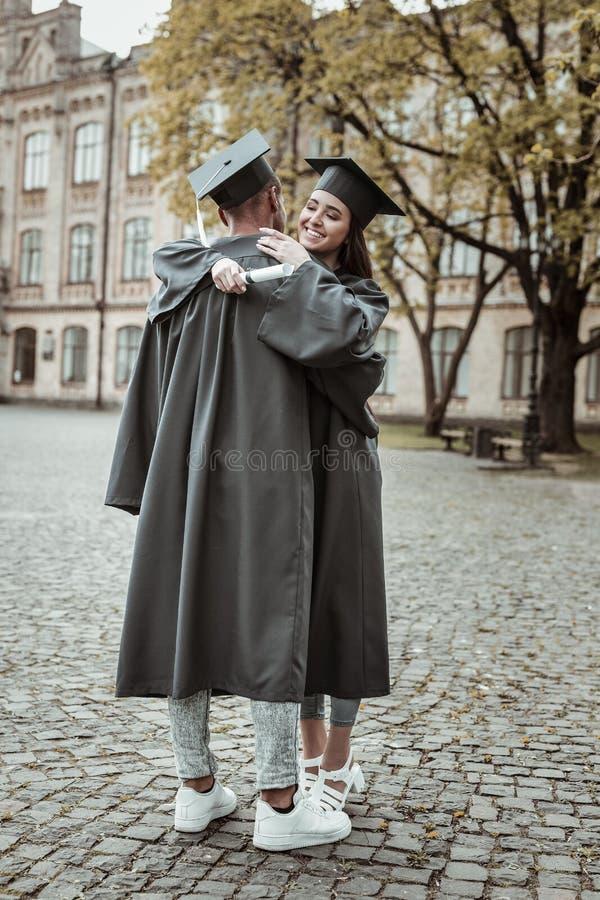 穿毕业的快乐的国际学生制服 免版税库存照片