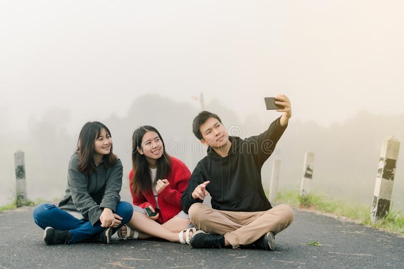 穿毛线衣的一个小组三个亚裔朋友使用selfie电话拍在旅游景点的照片 ?? 库存照片